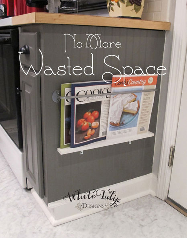 """Thành tủ đựng đồ: Hãy để những quyển tạp chí hoặc sách dạy nấu ăn của bạn ở một nơi dễ lấy (mà không để chúng bị bẩn hay rách) bằng cách lắp một cái giá đỡ trên thành tủ đựng đồ đặt dưới đất. Những chỗ như thế quá thấp để bạn có thể đựng những vật dụng được dùng thường xuyên nhưng là một nơi tuyệt vời để đựng những vật dụng dễ bị """"mất tích"""" trong đống lộn xộn của căn bếp nhà bạn."""